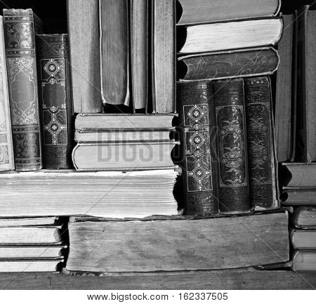 vintage books on wooden shelf in black and white.