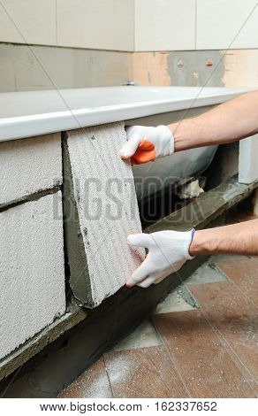 Worker places aerocrete blocks and forms the sidebar bath.