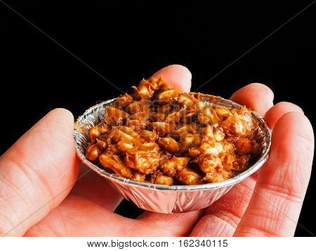 Person Holding Puffed Rice With Chocolate Cake In Aluminum Cup, On Black