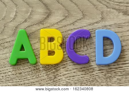 Capital letters A B C D in flat colorful plastic letter toys on textured gray wooden surface