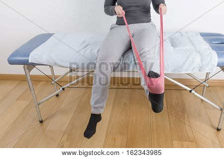 Patient Is Doing Therapy With An Elastic Band For Strengthening