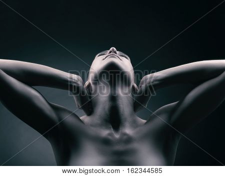 Female silhouette. Close-up of a woman neck with his hands behind his head