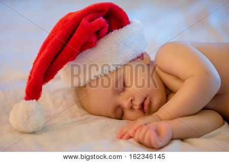 Beautiful little baby n a Christmas hat sleeping on bed.