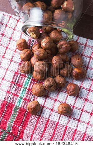 Hazelnuts in a jar on a vintage kitchen dishcloth. Brown wooden table. Closeup. Vegan healthy food concept.