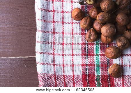 Hazelnuts on a vintage kitchen dishcloth. Brown wooden table. Flat lay top view. Copy space on the left. Vegan healthy food concept.