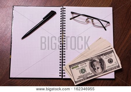 glasses black pen note book page and money a place for records business plan money background hundred dollar bills front side. background of dollars new hundred-dollar bil face the evolution of the bill in one hundred dollars copyspace