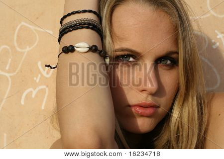 Punk girl leaning against graffiti wall
