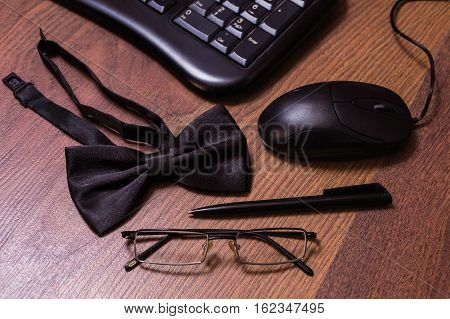 keyboard and mouse glasses black bowtie black pen note book page and money a place for records business plan money background hundred dollar bills front side. background of dollars copyspace