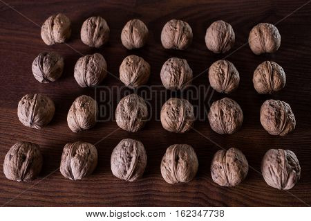 walnuts on a dark background conceptual photography walnuts lie in a row in a heap