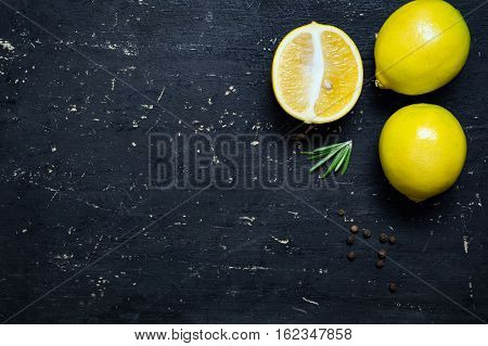 Fresh lemons and rosemary on scratched black background with copy space for text