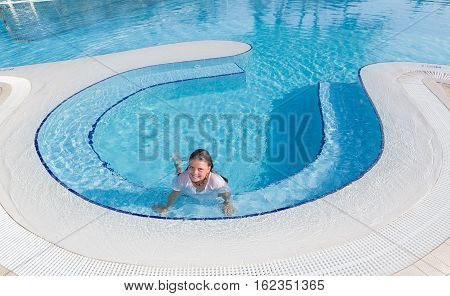 pretty joyful happy little girl swimming and enjoying her leisure time in the pool