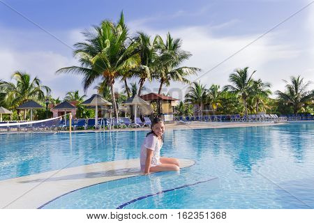 Cayo Coco island, Memories Carib resort, Cuba, June 30, 2016, joyful smiling happy little girl sitting on the edge of swimming pool on early morning at Memories Carib resort