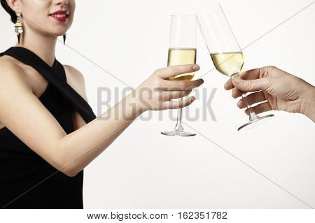 Woman celebrating and clang glasses together with champagne. Party concept. White background