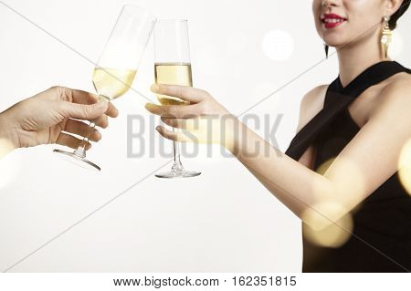 Woman celebrating and clang glasses together with champagne. White background with flares