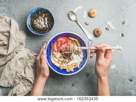 Healthy breakfast bowl. Yogurt, granola, seeds, fresh and dry fruits and honey in blue ceramic bowl in woman' s hands over grey background, top view. Clean eating, detox, dieting food concept