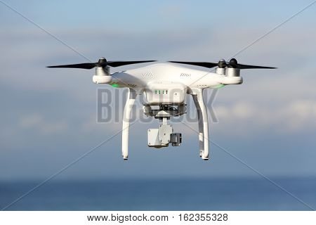 KAGAWA, JAPAN - DECEMBER 15, 2016: White remote controlled Drone Dji Phantom 3 equipped with high resolution video camera hovering in air with shore
