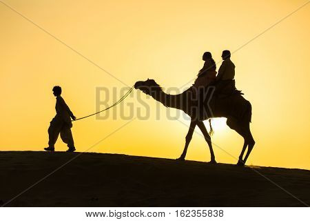 Jaisalmer, India - March 13, 2016: Rajasthan travel background - camel silhouette in dunes of Thar desert on sunset. Jaisalmer, Rajasthan, India