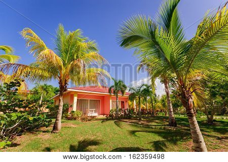 Cayo Coco island, Memories Carib hotel, June 30, 2016, amazing beautiful, gorgeous view of resort bungalow house standing in tropical garden against blue sky background on sunny day