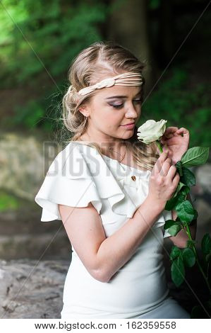 beautiful girl sniffing white rose in the Park