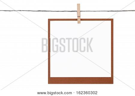 Blank instant photo hung on rope with clothespin