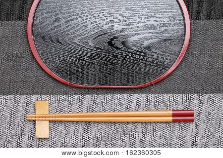 Chopsticks and empty tray on table background