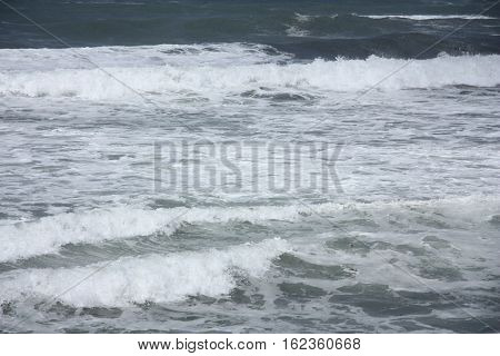 waves roll into the foamy shore line