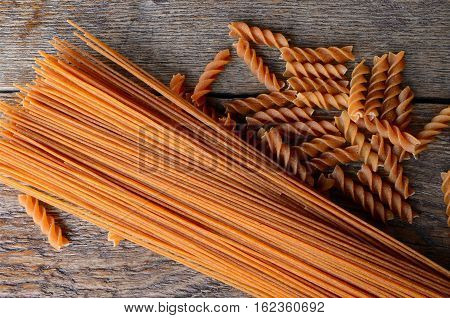 A top view image of wholewheat spaghetti and spiral pasta on an old wooden table top.