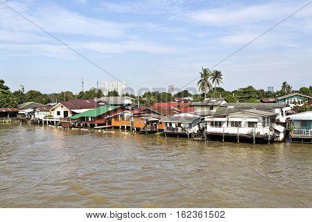 BANGKOK, THAILAND - November 4, 2016: Modest living style with houses on stilts along the banks of the Chao Phraya River in Bangkok Thailand