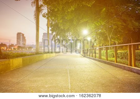 blur concrete bicycle way in park to exercise and relax. abstract blurred background sunrise