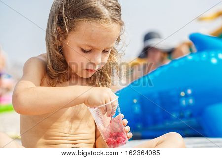 Beautiful boy is eating raspberries on the beach