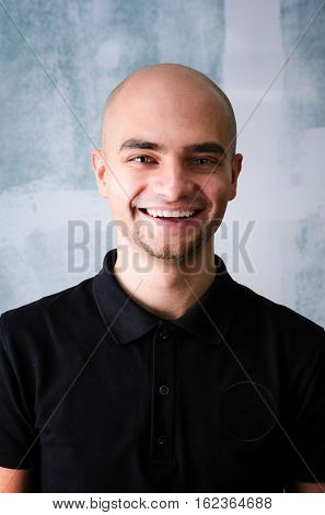 Portrait of young adult happy man agaist grunge wall