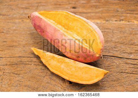 fresh cut orange potato on wooden table