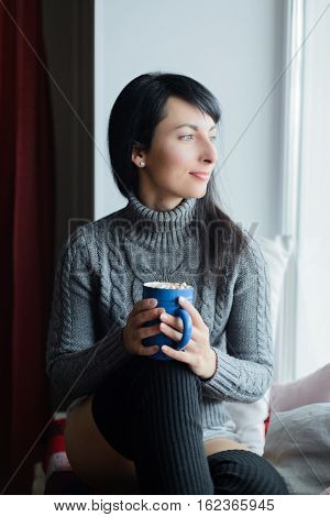 Young woman in knitted woolen socks and sweater sitting on windowsill with mug of cocoa