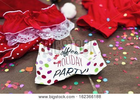 a pair of red panties ornamented with white lace, a pair of mens underpants, a santa hat and a signboard with the text office holiday party on the floor all sprinkled with confetti, after a party