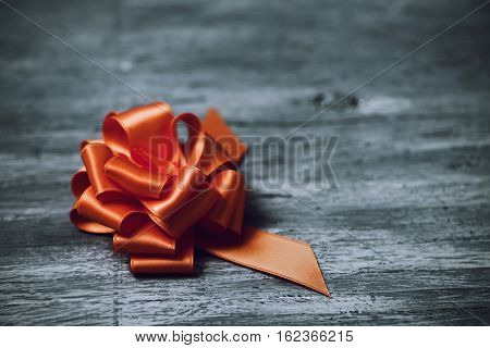 an orange satin gift ribbon bow on a rustic wooden surface, with a negative space