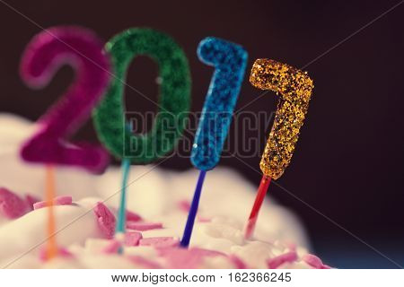 closeup of four glittering numbers of different colors forming the number 2017, as the new year, topping a cake