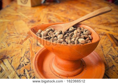 Coffee beans in a pottery cup., Raw.