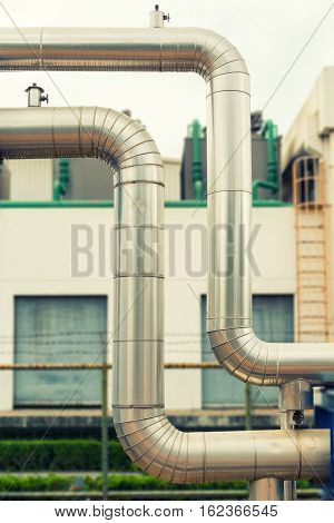 Omega loop steam pipeline on cooling tower background.