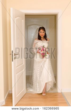 Lovely young bride entering the room in her traditional wedding dress