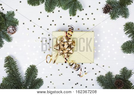 Christmas presents with golden ribbon on white wooden background in a frame made of fir branches with canes. Flat lay style
