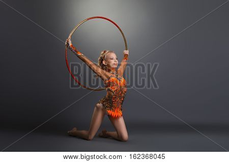 Young gymnast girl in bright leotard performing with hoop on grey studio background