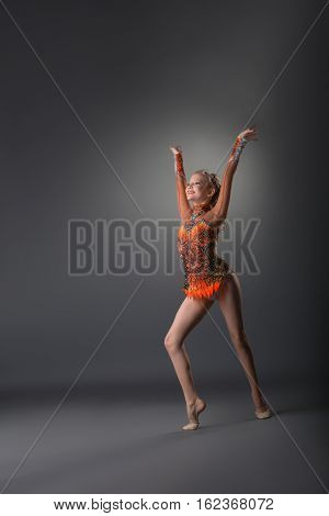 Full length of young athletic gymnast girl in bright leotard exercising on grey studio background