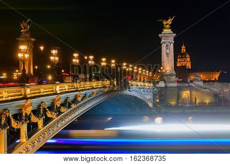 Bridge Pont Alexandre III in Paris at night with light trails of passing boats on the Seine
