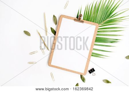 clipboard with empty copy space blank golden pen and clips petals and palm branch on white background. flat lay top view