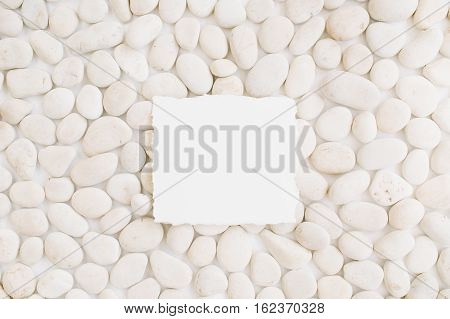 Blank with copy space on neutral pattern of beige stones. Flat lay top view
