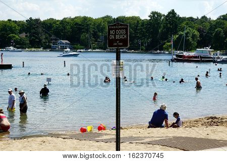 HARBOR SPRINGS, MICHIGAN / UNITED STATES - AUGUST 3, 2016: A sign indicates that dogs are not allowed on the Zorn Park Beach at any time.