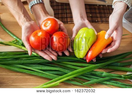 Women preparing dinner in a kitchen holding vegetables in hands dieting healthy food cooking at home