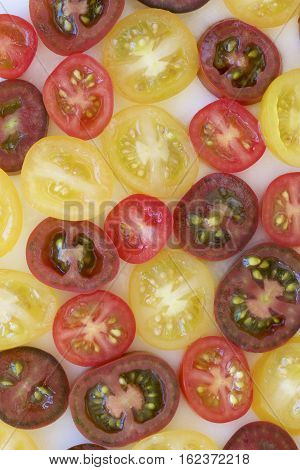Tomato medley of different colours set out in halves.