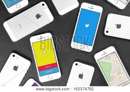 Apple iPhone 5s smartphones lying on leather surface