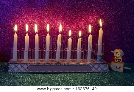 Jewish menorah with candles and dreidels are traditional symbols for Hanukkah Holiday